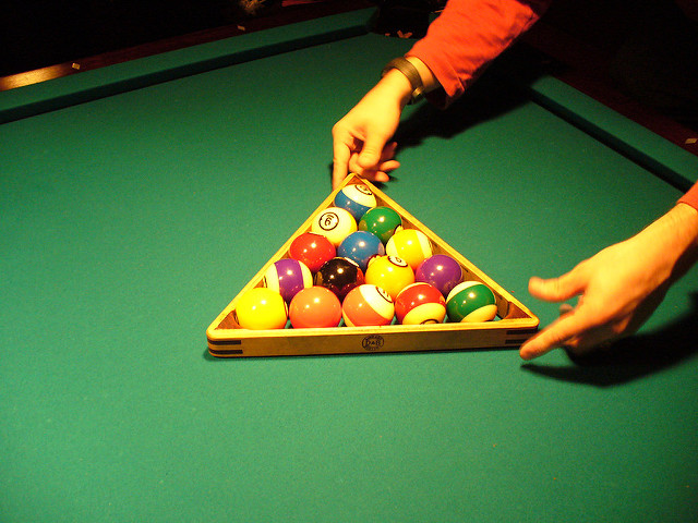 Man setting up an 8-ball pool rack